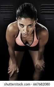 young attractive sexy latin sport woman posing in fierce and bad ass face expression with fit slim body isolated on gym locker room sweating in healthy lifestyle and fitness concept