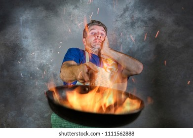 young attractive and shocked messy home cook man with apron holding pan in fire burning the food in kitchen disaster and unskilled and unexperienced terrible home cook at domestic cooking