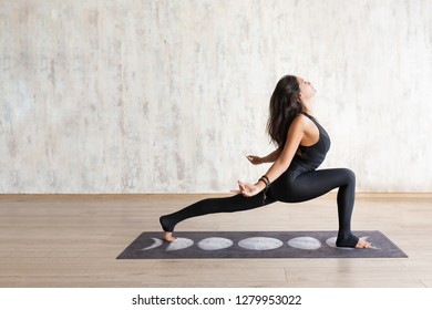 Young attractive slender stretching body in yoga asana against concrete wall. Focused asian girl wearing black sportswear standing in asana, pose. Practicing yoga at home. Side view.