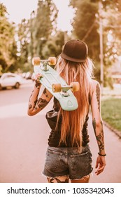 Young attractive slim girl with tattoos, piercing and long hair walking in the street with green longboard.