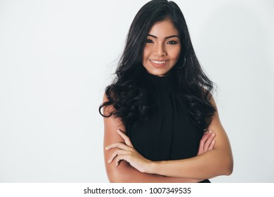 Young attractive smart business woman confidently smiles with arms folded over white background