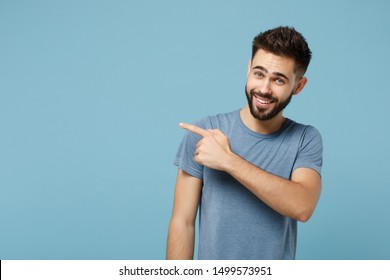 Young attractive smiling funny man in casual clothes posing isolated on blue background, studio portrait. People sincere emotions lifestyle concept. Mock up copy space. Pointing index finger aside