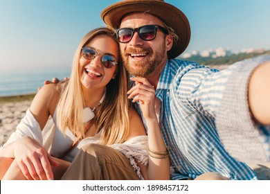 young attractive smiling happy man and woman in sunglasses sitting on sand beach taking selfie photo on phone camera, romantic couple by the sea on sunset, boho hipster style outfit