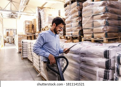 Young attractive smiling supervisor pushing forklift and holding tablet to check on goods for exporting.
