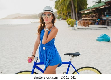 young attractive smiling woman in blue dress walking on tropical beach with bicycle wearing hat and sunglasses traveling on summer vacation in Thailand, boho fashion style