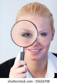 young attractive Smiling woman looking into a magniying glass