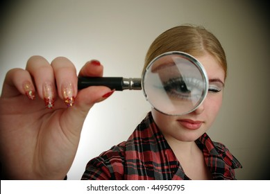 young attractive Smiling woman looking into a magnifing glass