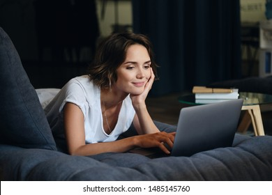 Young attractive smiling woman lying on sofa happily working on new project with laptop in modern office
