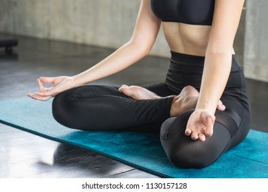 Young attractive smiling woman practicing yoga, sitting.Young beautiful woman practicing yoga and gymnastic. Wellness concept in gym