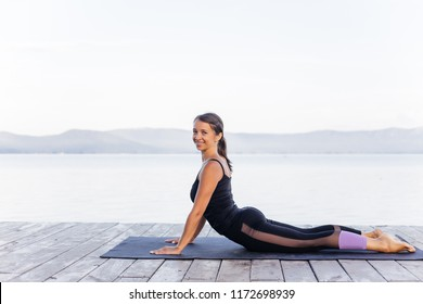Young attractive smiling woman practicing yoga on a lake