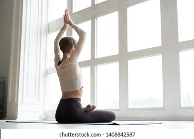 Young attractive smiling woman practicing yoga, sitting in Half Lotus exercise, Ardha Padmasana pose, working out, wearing sportswear
