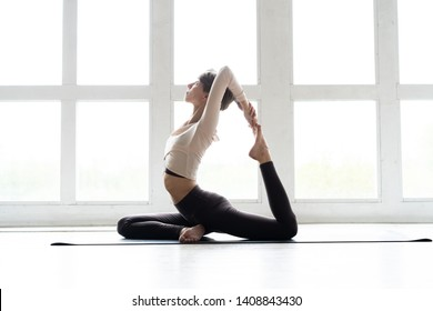 Young attractive smiling woman practicing yoga, sitting in One Legged King Pigeon exercise, Eka Pada Rajakapotasana pose, working out, wearing sportswear, brown pants, bra, indoor full length, home