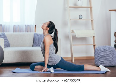 Young attractive smiling woman practicing yoga at home