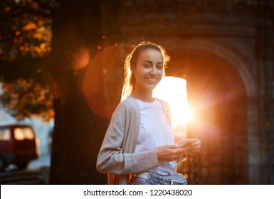 young attractive smiling woman is standing on the street in a beautiful sunset backlight and using mobile phone.