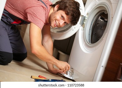 Young attractive smiling worker in uniform fixing washing machine, background
