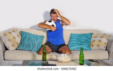 young attractive soccer fan and supporter man at home sofa couch watching football game on TV dejected and sad after team defeat loss and defeat drinking beer in broadcast live game
