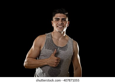 young attractive sport man with big and strong athletic body smiling happy wearing sweaty singlet giving thumb up in join my fitness club gym concept isolated on black background