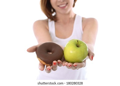 Young attractive sport Woman smiling and holding Apple and Chocolate Donut in Hands in healthy versus junk food dessert choice isolated on White background