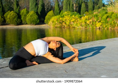Young attractive sportswoman practicing yoga, doing the exercise Revolved Head to Knee Forward, Parivrtta Janu Sirsasana pose, exercising, in the morning and a lake in the background.
