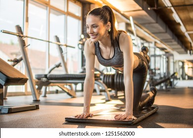 Young attractive sporty girl warming up, practicing yoga, doing Bird dog exercise, Donkey Kick pose at gym