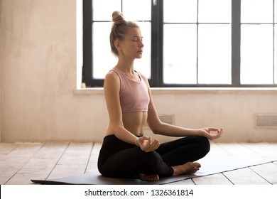 Young attractive sporty woman doing yoga Sukhasana exercise, meditating in Easy Seat pose, working out, wearing sportswear, indoor full length, white yoga studio. Well being, wellness concept