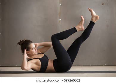 Young attractive sporty woman doing crisscross, bicycle crunches, fitness exercise, working out, wearing black sportswear, cool urban style, full length, grey studio background, side view