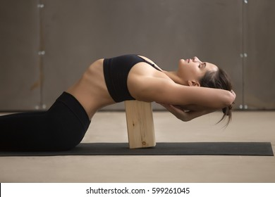 Young attractive sporty woman practicing yoga, stretching in Matsyasana using wooden block, Fish pose, exercise for spine and shoulders flexibility working out, cool urban style, grey studio, closeup