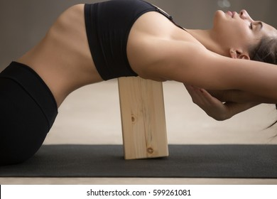 Young attractive sporty woman practicing yoga, stretching in Matsyasana using wooden block, Fish pose, exercise for spine and shoulders flexibility, working out, cool urban style, grey studio, closeup