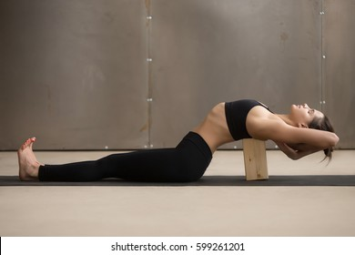 Young attractive sporty woman practicing yoga, stretching in Matsyasana using block, Fish pose, exercise for spine and shoulders flexibility, working out, cool urban style, full length, grey studio