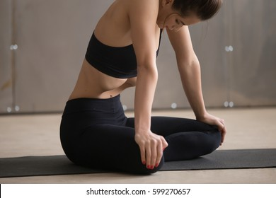 Young attractive sporty woman practicing yoga, sitting in Sukhasana pose, making Upward Abdominal Lock, Uddiyana Bandha exercise, working out, black sportswear, cool urban style, close up, grey studio