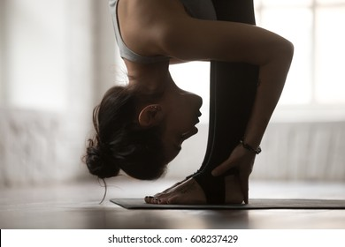 Young attractive sporty woman practicing yoga, standing forward bend exercise, head to knees, uttanasana pose, working out, wearing sportswear, white loft studio background, side view, close up