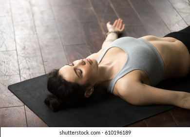 Young attractive sporty woman practicing yoga, lying on black mat on the floor in Dead Body, Corpse exercise, Savasana pose with her eyes closed, resting after working out, close up portrait