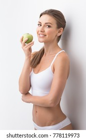 Young attractive sporty woman in white underwear holding green apple