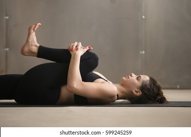 Young attractive sporty yogi woman practicing yoga, stretching in Knees to Chest, Apanasana exercise, working out wearing black sportswear, cool urban style, grey studio background, closeup, side view