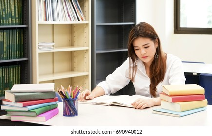 Young attractive student with color of pencil sitting at desk in university library studying books. with colorful of books.