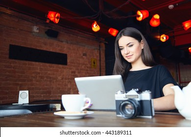 Young attractive student girl in black t-shirt with cute smile working on laptop while sitting alone in coffee shop during free time. Female bloger freelancer photographer. Lifestyle, leisure time