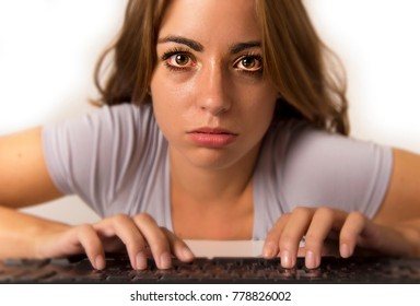 young attractive student girl or working woman sitting at computer desk in stress with tired red eyes after long hours working looking at the screen in vision health care and laptop internet addiction