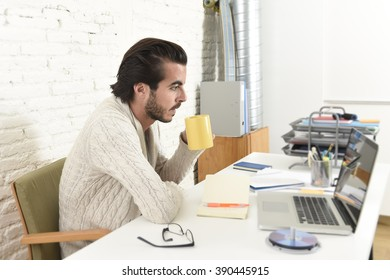 young attractive student preparing university project drinking coffee or hipster style freelancer businessman working with laptop computer analyzing project at home office studio