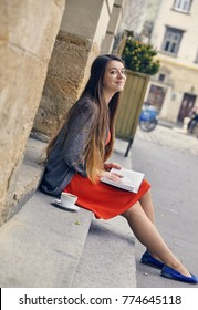 Young attractive student in red dress studying and reading a book. Relax, rest, education concept, recreation .
