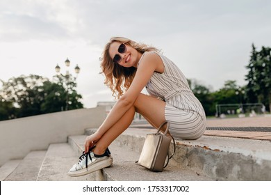 young attractive stylish blonde woman sitting in city street in summer fashion style dress wearing sunglasses, purse, silvers sneakers footwear style