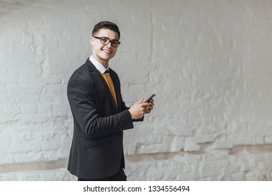 Young  attractive stylish businessman holding his phone at ofice and smiling. Lifestyle!