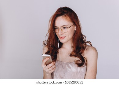 Young attractive stylish caucasianred headed freckled girl posing in studio using smartphone reading, listening music and communicate online