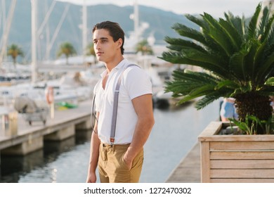 Young Attractive stylish man walks along the pier with yachts and hotels. Portrait of Male model.