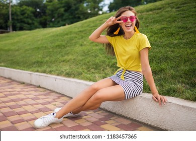 young attractive stylish smiling woman having fun in city park, positive, emotional, wearing yellow top, striped mini skirt, pink sunglasses, white sneakers, summer style fashion trend, peace sign