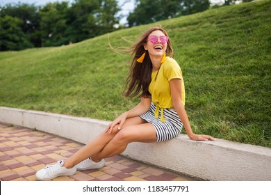 young attractive stylish smiling woman having fun in city park, positive, emotional, wearing yellow top, striped mini skirt, pink sunglasses, white sneakers, summer style fashion trend, long legs