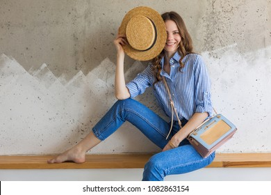 young attractive stylish woman sitting at wall background, straw hat, wearing blue cotton shirt, jeans, casual outfit, hipster style, spring summer fashion trend, smiling face, happy mood, relaxed