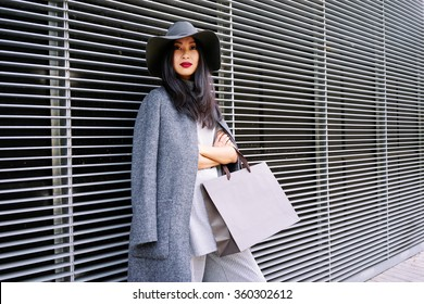 young attractive stylishly-dressed Asian girl posing and holding a blank paper bag with empty space for your text or logo