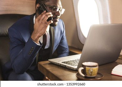 Young attractive and successful African American businessman with glassies talking on the phone and working while sitting in the chair of his private business plane