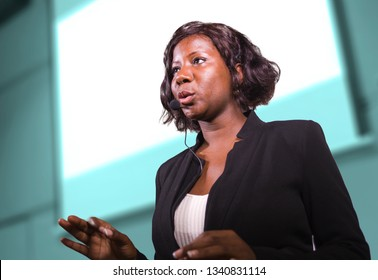 young attractive and successful black African American business woman with headset speaking in auditorium at corporate training event or seminar giving motivation and success coaching conference