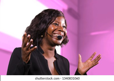 young attractive and successful black afro American business woman with headset speaking in auditorium at corporate training event or seminar giving motivation and success coaching conference